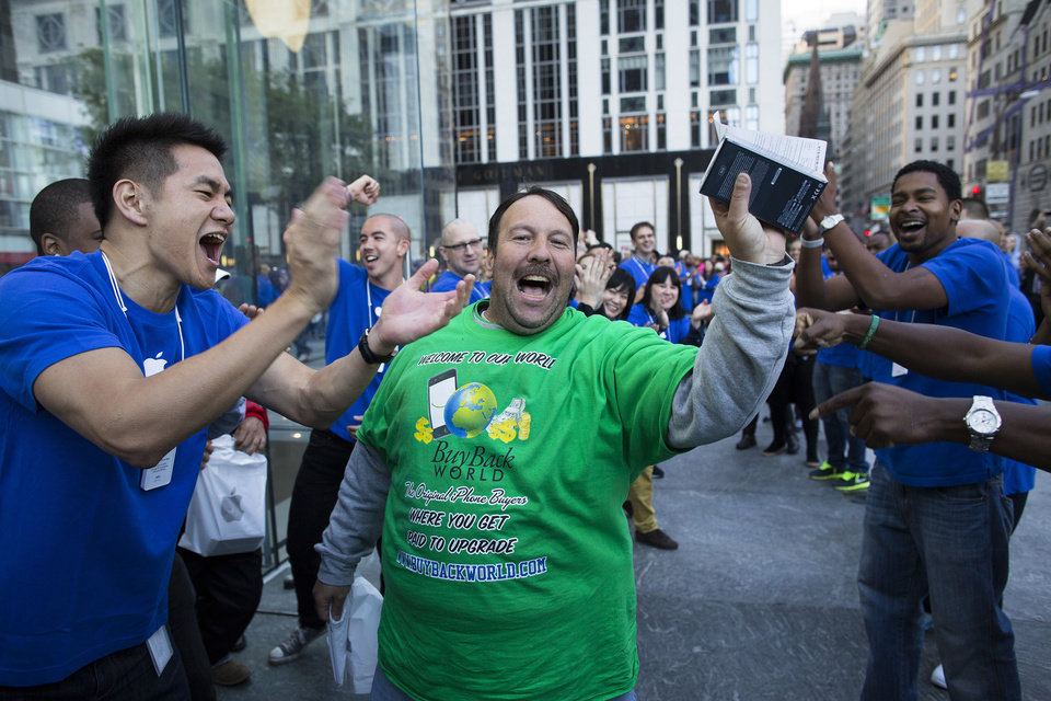 Photo -   Greg Packer, 49, is cheered on as he celebrates with his newly purchased iPhone 5 in hand outside the Fifth Avenue Apple store, Friday, Sept. 21, 2012, in New York. Hundreds of people waited in line through the early morning to be among the first to get their hands on the highly anticipated phone. (AP Photo/John Minchillo)