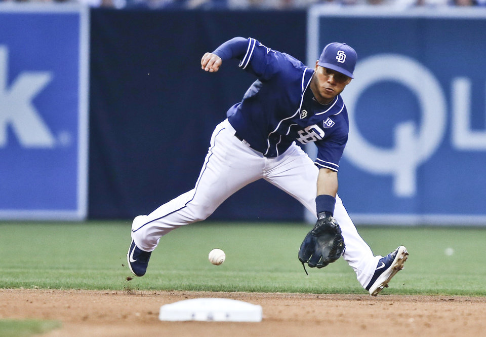 Photo - San Diego Padres shortstop Alexi Amarista goes into the hole behind second to take a hit away from New York Mets' Ruben Tejada in the sixth inning of a baseball game Saturday, July 19, 2014, in San Diego.   (AP Photo/Lenny Ignelzi)