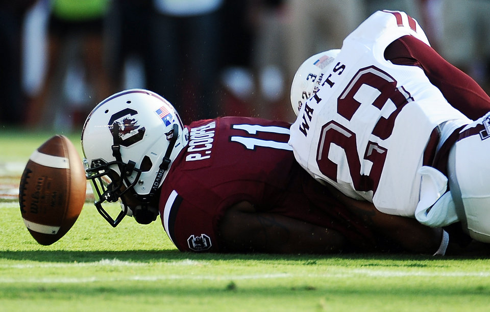 Photo - South Carolina wide receiver Pharoh Cooper (11) drops a pass as Texas A&M defensive back Armani Watts (23) defends during the first half of an NCAA college football game on Thursday, Aug. 28, 2014, in Columbia, S.C. Texas A&M won 52-28. (AP Photo/Rainier Ehrhardt)