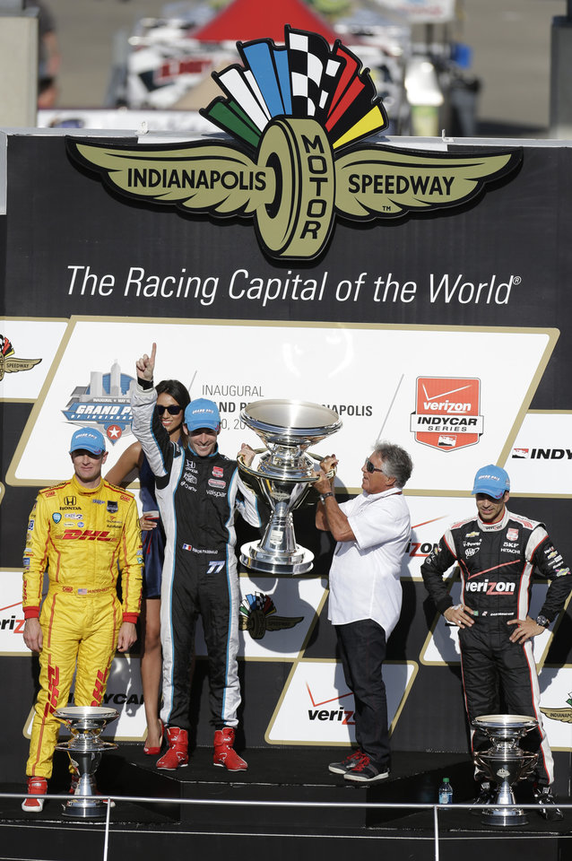 Photo - Former Indianapolis 500 champion Mario Andretti, right, helps Simon Pagenaud, of France, hoist the trophy after winning the inaugural Grand Prix of Indianapolis IndyCar auto race at the Indianapolis Motor Speedway in Indianapolis, Saturday, May 10, 2014. Ryan Hunter-Reay, left, finished second and Helio Castroneves, of Brazil, came in third. (AP Photo/Darron Cummings)