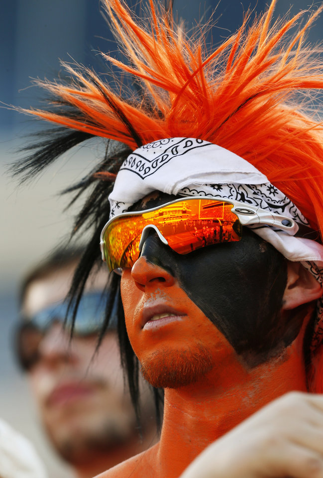 Photo - OSU student Conner Bayliff of Gardner, Kansas, watches OSU warm up before a college football game between Oklahoma State University (OSU) and Savannah State University at Boone Pickens Stadium in Stillwater, Okla., Saturday, Sept. 1, 2012. Photo by Nate Billings, The Oklahoman