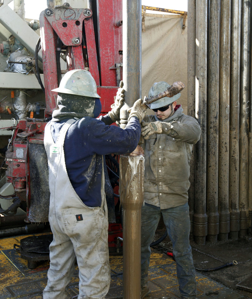 Photo - Workers add a new section of drill stem on a Devon Energy drilling rig a few miles east of Perry, OK, Friday, January 17, 2014,  Photo by Paul Hellstern, The Oklahoman