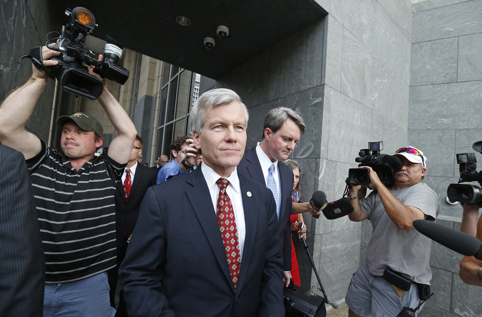Photo - Former Virginia Gov. Bob McDonnell, center, leaves the federal courthouse in Richmond, Va., with his lawyer John L. Brownlee on the second day of his and his wife Maureen's corruption trial, Tuesday, July 29, 2014. (AP Photo/Richmond Times-Dispatch, Alexa Welch Edlund)