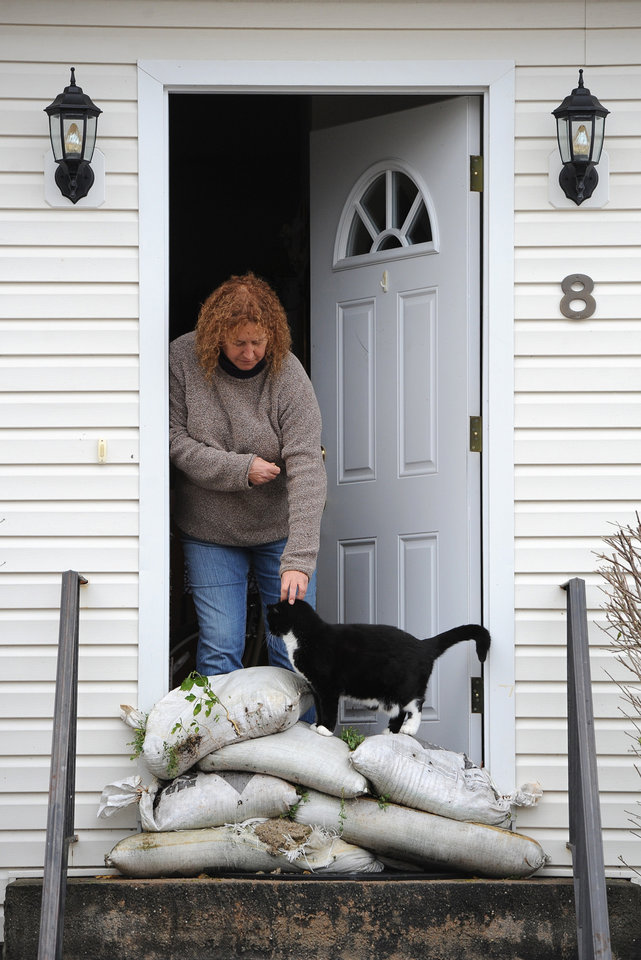 Paula Bacco pets her cat, Phoebe, in her doorway barricaded with sand bags for protection against flooding from Sandy on Tuesday, Oct., 30, 2012, in Bayville, N.Y. The basement of Bacco\'s home was flooded by the storm that made landfall Monday, causing multiple fatalities, halting mass transit and cutting power to more than 6 million homes and businesses. (AP Photo/Kathy Kmonicek) ORG XMIT: NYKK109
