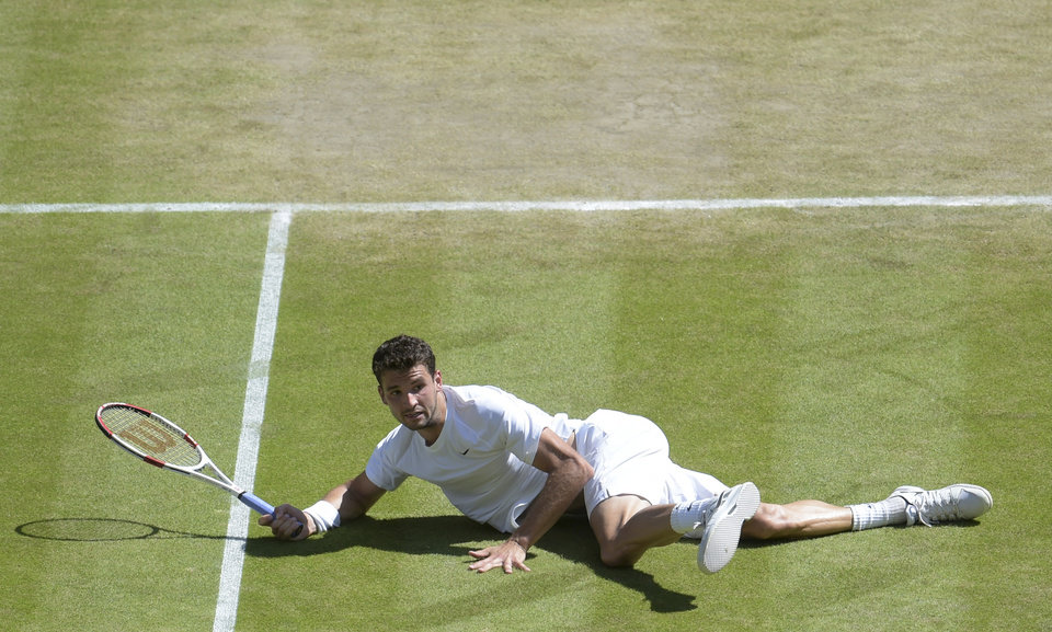Photo - Grigor Dimitrov of Bulgaria falls to the ground as he plays against Novak Djokovic of Serbia during their men's singles semifinal match at the All England Lawn Tennis Championships at Wimbledon, London, Friday, July, 4, 2014. (AP Photo/Facundo Arrizabalaga, Pool)