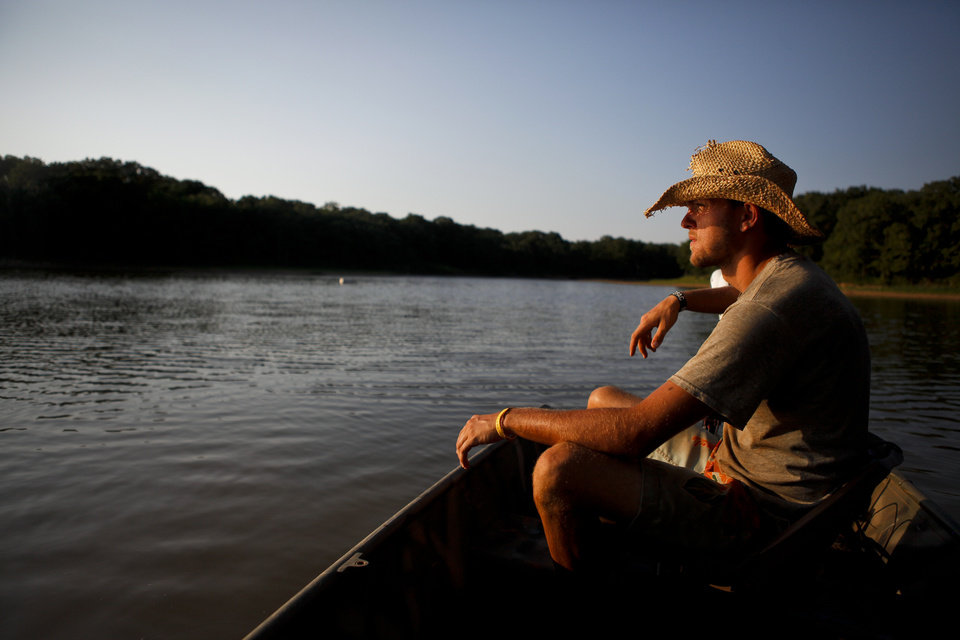 Photo - Tell Judkins looks out over the water as he heads out on Lake McMurtry near Stillwater on Friday, July 8, 2011. The group was looking for catfish to enter into the 12th Annual Okie Noodling Tournament in Pauls Valley, Okla. Photo by Zach Gray, The Oklahoman ORG XMIT: KOD