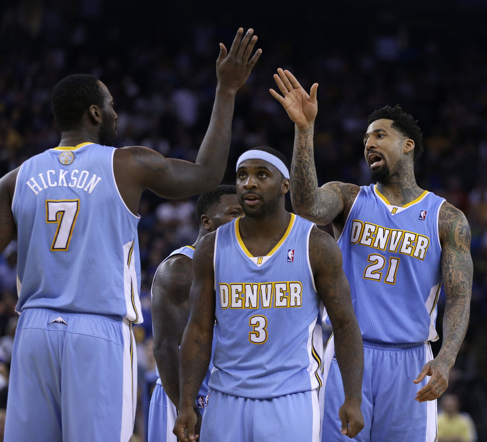 Photo - From left, Denver Nuggets' J.J. Hickson, Ty Lawson, and Wilson Chandler (21) celebrate during a time out against the Golden State Warriors during the second half of an NBA basketball game on Wednesday, Jan. 15, 2014, in Oakland, Calif. (AP Photo/Ben Margot)