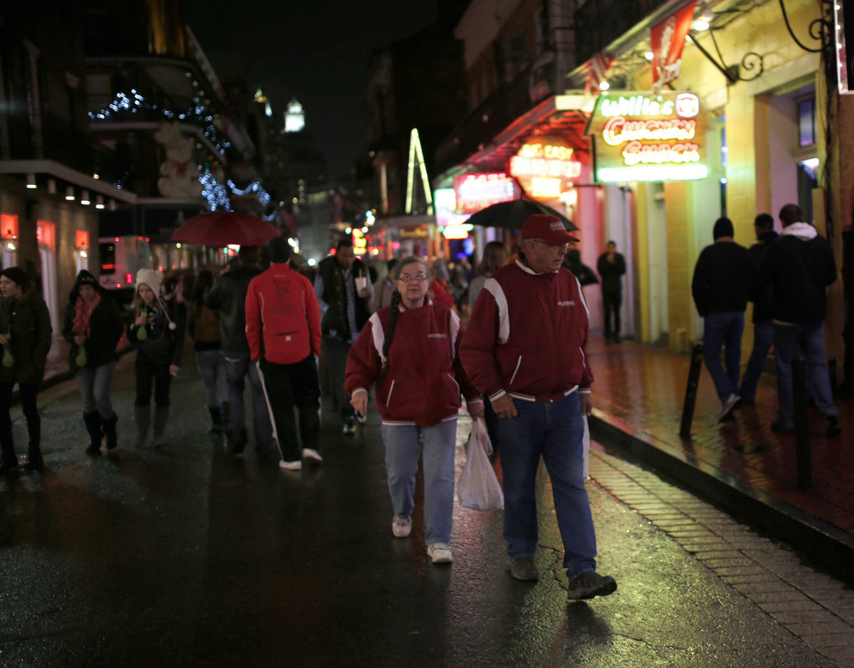 Photo - Oklahoma fans Ken and Becky Clarr of Davis, Okla., walk down Bourbon Street in the French Quarter New Year's Eve, Tuesday, Dec. 31, 2013 in New Orleans. Photo by Sarah Phipps, The Oklahoman