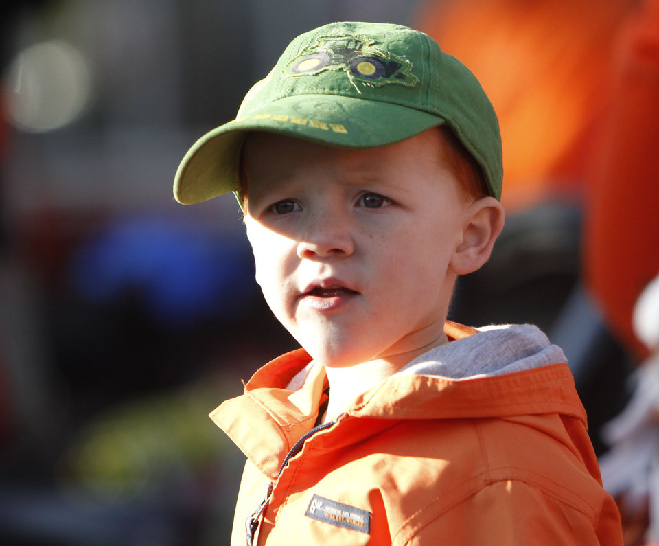 Photo - Three year old Maguire Bugg watches the Oklahoma State Cowboy's homecoming parade in downtown Stillwater, OK, Saturday, Oct. 29, 2011. By Paul Hellstern, The Oklahoman