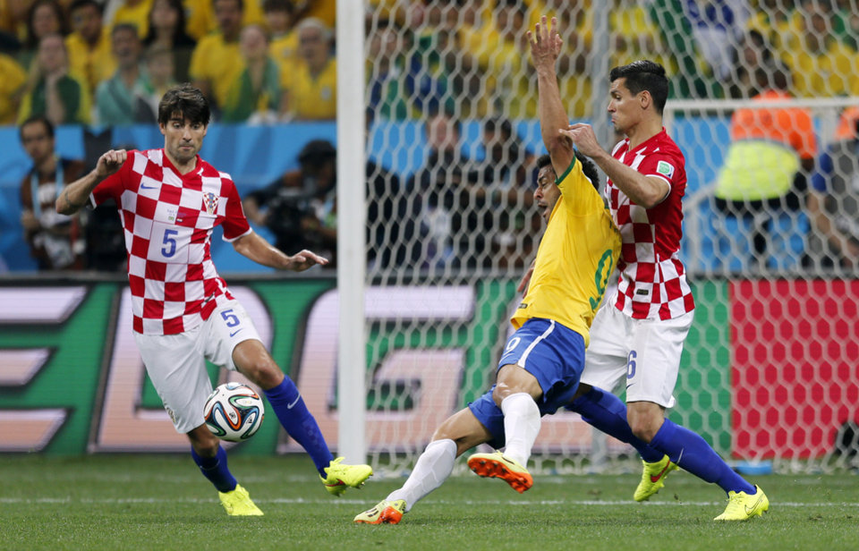 Photo - Brazil's Fred, center, falls next to Croatia's Dejan Lovren, right, as Croatia's Vedran Corluka, left, watches during the group A World Cup soccer match in the opening game of the tournament at Itaquerao Stadium in Sao Paulo, Brazil, Thursday, June 12, 2014. Brazil was awarded a penalty kick after Lovren was issued a yellow card on the play leading to a goal by Brazil's Neymar. (AP Photo/Frank Augstein)