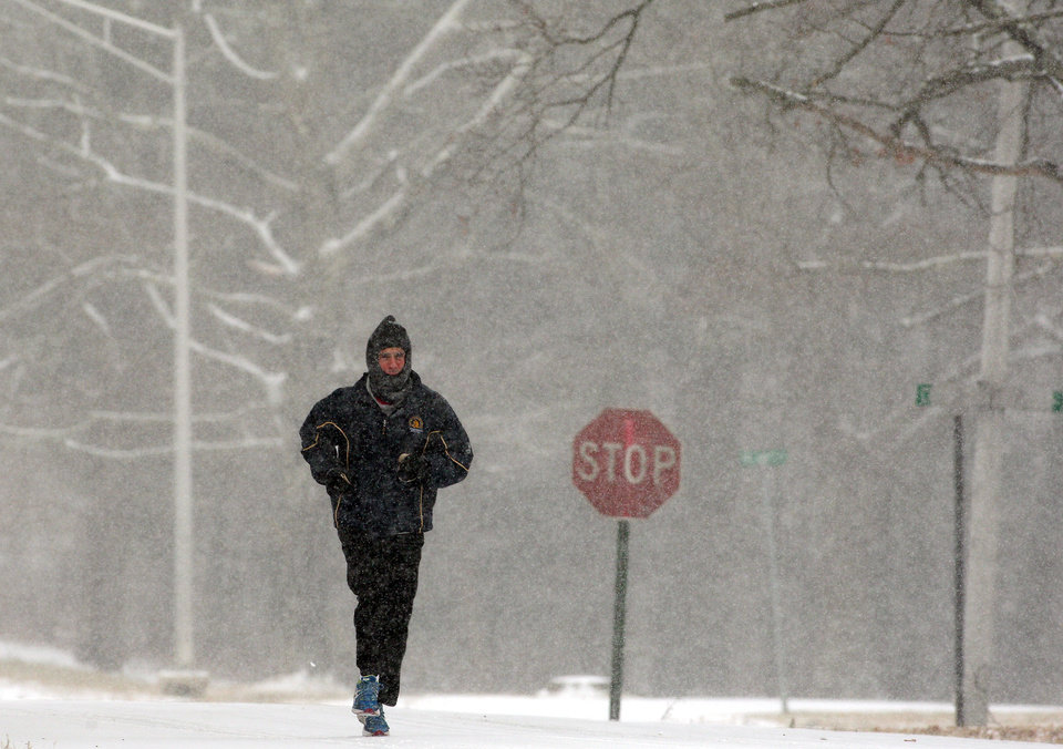 Photo - Greg Spadavecchia jogs as snow starts to fall in Morris Plains, N.J. on Tuesday, Jan. 21, 2014.  A storm is expected to hit the northern New Jersey region throughout the day. Because of hazardous driving conditions New Jersey Gov. Chris Christie's inauguration party at Ellis Island was cancelled.  (AP Photo/The Daily Record, Bob Karp )  NO SALES