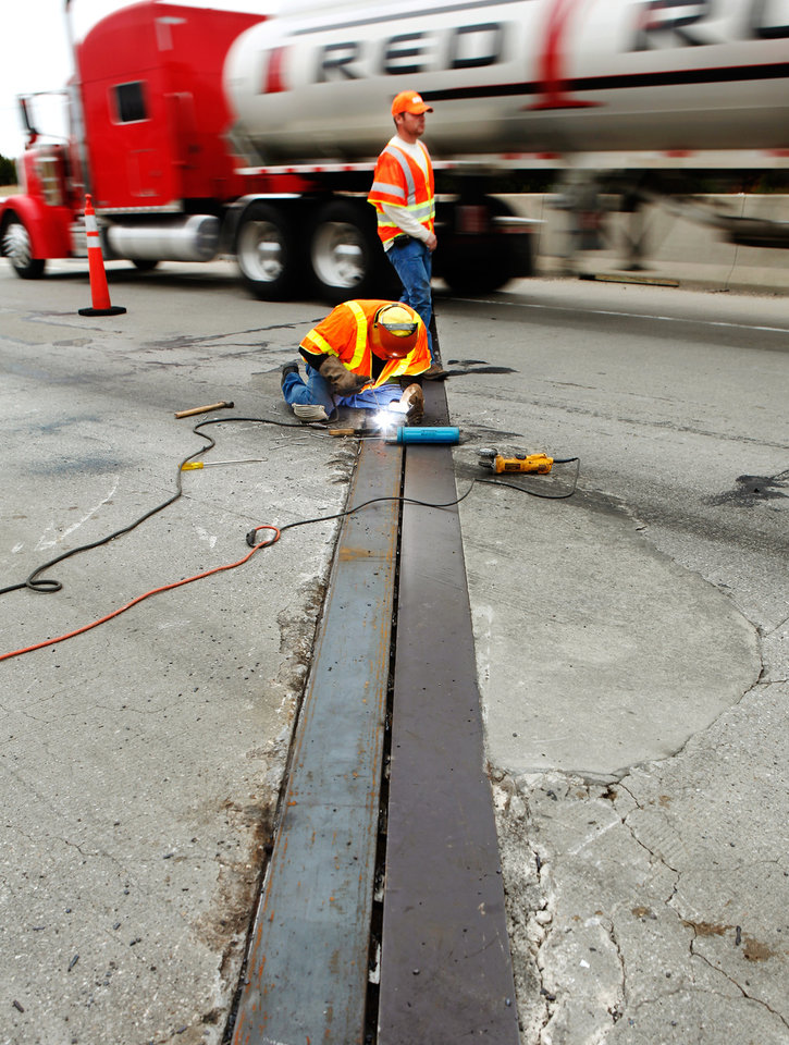 Tim Keefer welds new sections of an expansion joint on a bridge on Interstate 40 around noon Monday, Nov. 14, 2011. A section of the joint buckled earlier in the morning and maintenance crews were dispatched to the scene in the westbound lanes of I-40, about one quarter mile west of the US Highway 177 junction.  Traffic was merged into a single lane as repairs were made.  .  Photo by Jim Beckel, The Oklahoman