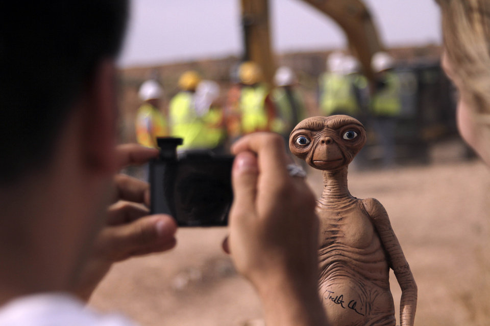 Photo - A man takes a photo of an E.T. doll in Alamogordo, N.M, Saturday, April 26, 2014. Producers of a documentary dug in an southeastern New Mexico landfill in search of millions of cartridges of the Atari 'E.T. the Extra-Terrestrial' game that has been called the worst game in the history of video gaming and were buried there in 1983. (AP Photo/Juan Carlos Llorca)