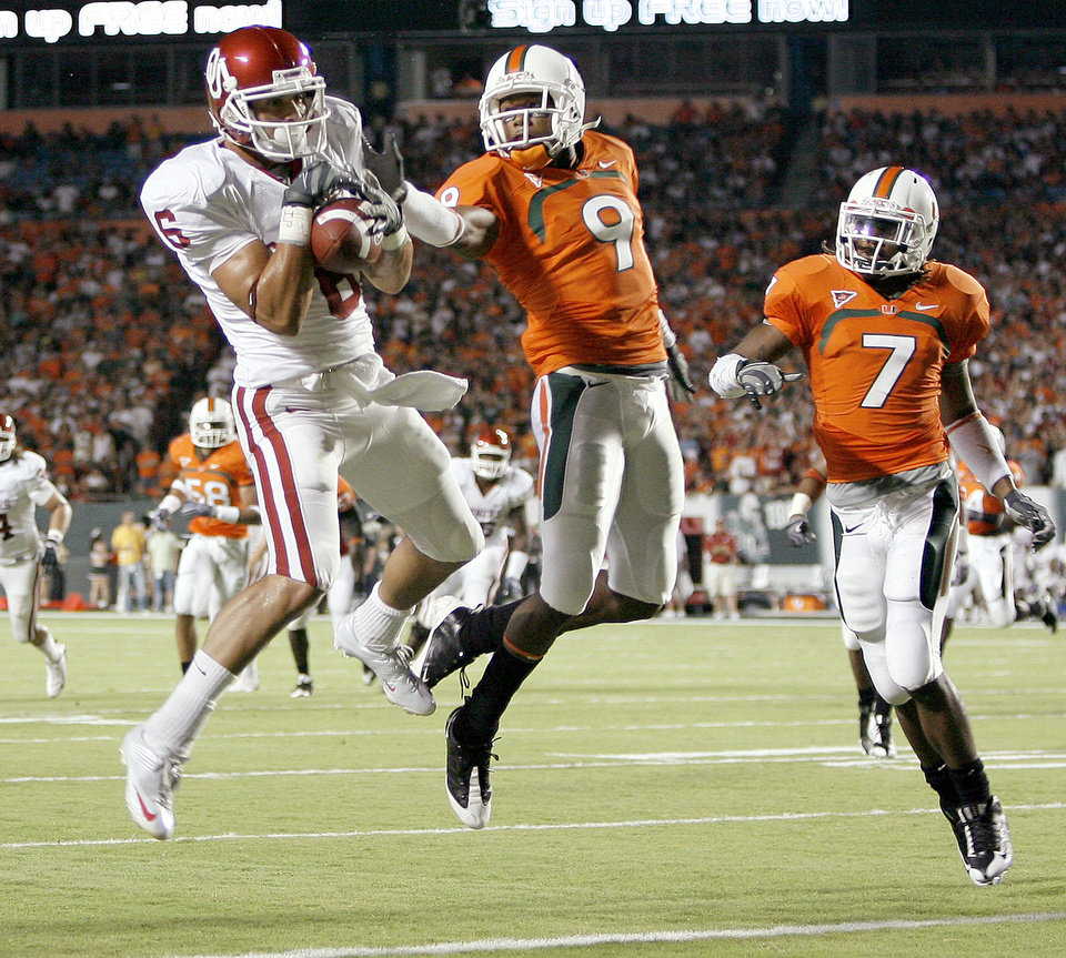 Photo - CAM KENNEY: OU's Cameron Kenney catches a touchdown pass beside Miami's Sam Shields, left, and Vaughn Telemaque during the college football game between the University of Oklahoma (OU) Sooners and the University of Miami (UM) Hurricanes at Land Shark Stadium in Miami Gardens, Florida, Saturday, October 3, 2009. Photo by Bryan Terry, The Oklahoman ORG XMIT: KOD