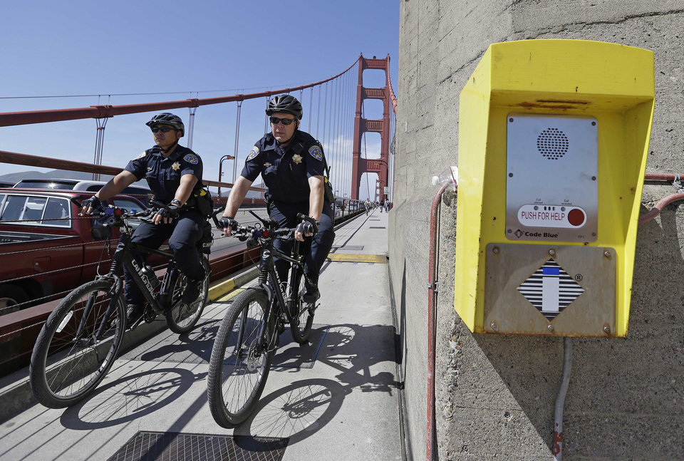 Photo - FILE - In this file photo taken Tuesday, April 30, 2013 California Highway Patrol officers Steve Bautista, left, and Sandro Salvetti, right, ride their bicycles past a crisis counseling call box during a patrol on the Golden Gate Bridge in San Francisco. On Friday, June 27, 2014, Golden Gate Bridge officials are expected to approve a funding package for a $76 million suicide barrier. (AP Photo/Eric Risberg)