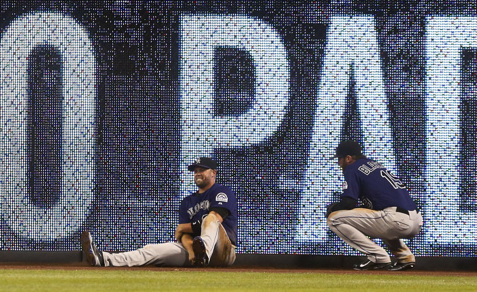 Photo - Colorado Rockies right fielder Michael Cuddyer holds his arm as teammate Charlie Blackmon squats next to him after Cuddyer crashed in the wall trying to make a catch in the fifth inning of a baseball game Monday, April 14, 2014, in San Diego. Cuddyer left the game. (AP Photo/Lenny Ignelzi)