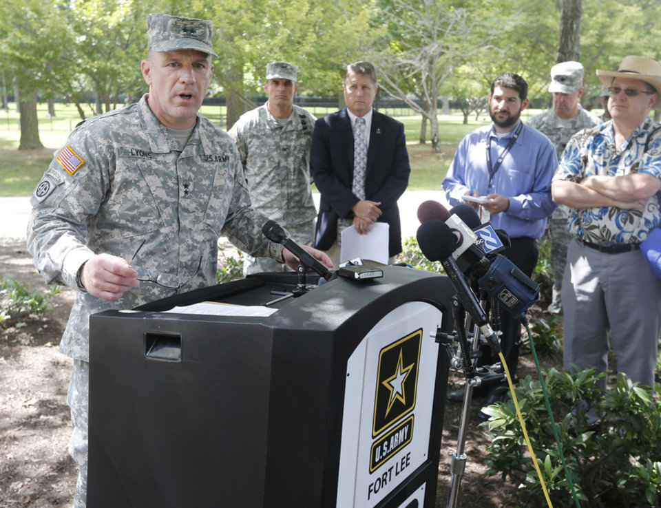 Photo - Army Major General Stephen Lyons speaks during a news conference at the base in Fort Lee, Va., Monday, Aug. 25, 2014.  A female soldier with a gun inside a key building at a Virginia Army base turned the weapon on herself, causing an injury, but didn't wound any others as the heavily trafficked base temporarily went on lockdown Monday morning.   (AP Photo/Steve Helber)