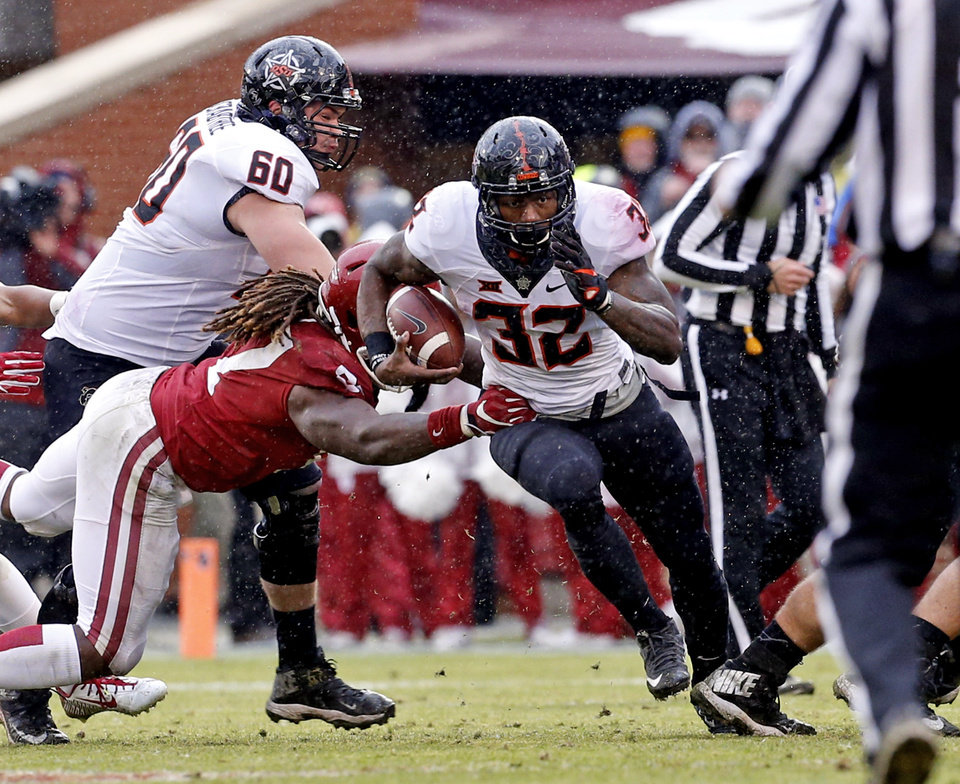Photo - Oklahoma State's Chris Carson (32) carries pursued by Oklahoma's D.J. Ward (87) during the second half of the Bedlam college football game between the Oklahoma Sooners (OU) and the Oklahoma State Cowboys (OSU) at Gaylord Family - Oklahoma Memorial Stadium in Norman, Okla., Saturday, Dec. 3, 2016. Photo by Steve Sisney, The Oklahoman