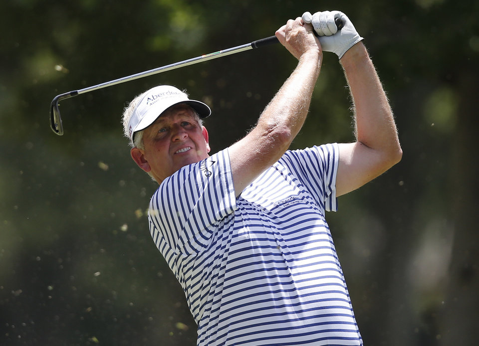 Photo - Colin Montgomerie hits from the fourth tee during the third round of the U.S. Senior Open golf tournament at Oak Tree National in Edmond, Okla., Saturday, July 12, 2014. (AP Photo/Sue Ogrocki)