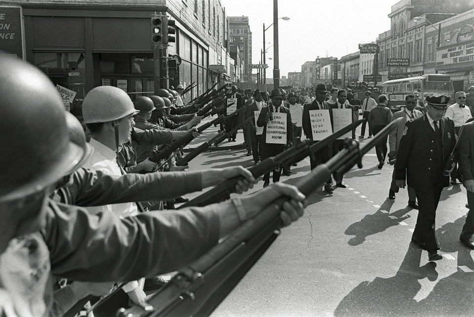Photo - FILE -In this March 29, 1968 file photo, striking Memphis sanitation workers march past Tennessee National Guard troops with fixed bayonets during a 20-block march to City Hall, one day after a similar march erupted in violence, leaving one person dead and several injured. Forty-five years after Martin Luther King Jr. was killed supporting a historic sanitation workers strike in Memphis, the city's garbage and trash collectors are fighting to hold on to jobs that some city leaders want to hand over to a private company. (AP Photo/Charlie Kelly, File)