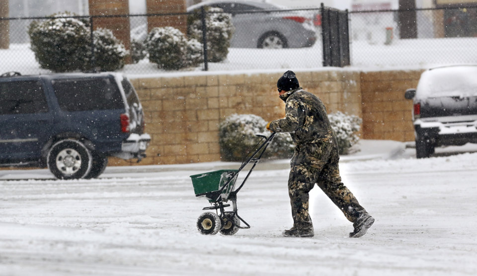 Photo - A man spreads de-icer pellets in the parking lot of a Walgreen's in Midwest City. Snow began falling in central Oklahoma around 7 Sunday morning, Feb. 2, 2014.   Photo by Jim Beckel, The Oklahoman