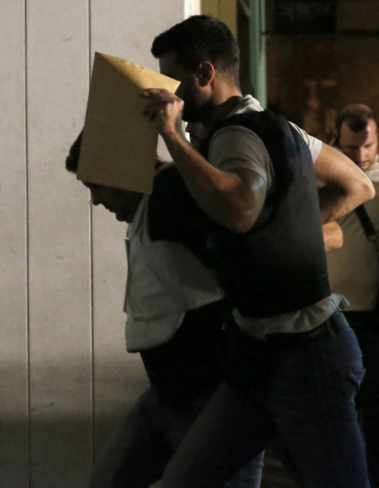 Photo - A policeman holds a envelop as he escorts a man, left, accused in the fatal stabbing of a 34-year-old musician described as an anti-fascist activist, at a court in Piraeus, near Athens, Greece, Wednesday, Sept. 18, 2013. Violent clashes broke out Wednesday in several Greek cities after the fatal incident earlier Wednesday, and the 45-year old accused man, who is not named in accordance with Greek law, appeared in court. (AP Photo/Petros Giannakouris)