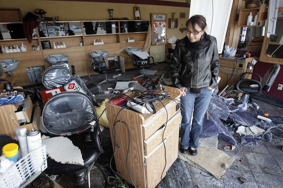 Tornado damage near the intersection of Rockwell and Northwest Expressway, Wednesday , February 11, 2009. Nieka Harms looks through her damaged Fantastic Sam's hair salon . By David McDaniel, The Oklahoman.