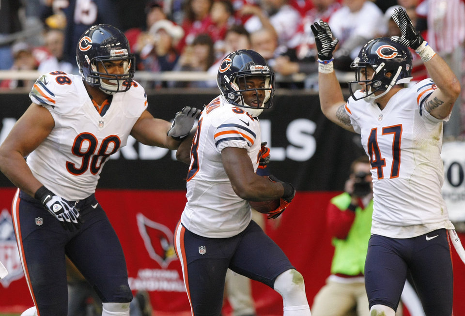 Photo - Chicago Bears defensive back Zack Bowman celebrates his touchdown with teammates Corey Wootton (98) and Chris Conte (47) during the first half of an NFL football game, Sunday, Dec. 23, 2012, in Glendale, Ariz. (AP Photo/Rick Scuteri)