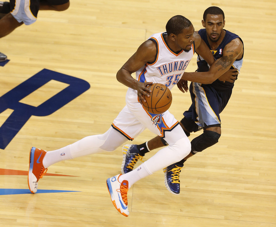 Photo - Oklahoma City's Kevin Durant (35) goes past Memphis' Mike Conley (11) during Game 1 in the first round of the NBA playoffs between the Oklahoma City Thunder and the Memphis Grizzlies at Chesapeake Energy Arena in Oklahoma City, Saturday, April 19, 2014. Photo by Nate Billings, The Oklahoman