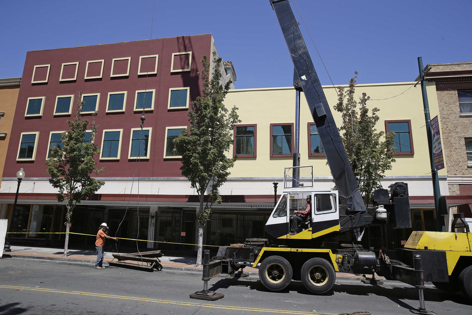 Photo - A crane lowers pieces from a collapsed elevator shaft outside an earthquake damaged former department store Tuesday, Aug. 26, 2014, in Vallejo, Calif. The historic blue-collar town of Vallejo is a short distance but a far cry from the touristy Napa Valley's vineyards and quaint towns, but when Sunday's big earthquake struck, it was not spared. The bayside city that twice was briefly the capital of California sustained more than $5 million in damage and dozens of injuries. It was the latest blow to a town that has weathered years of bankruptcy and is now beset by gangs and crime. (AP Photo/Eric Risberg)