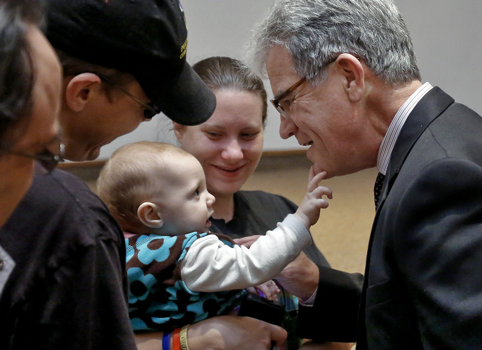 Photo - Nine-month-old Taylor Lozier touches U.S. Sen. Tom Coburn's face after he spoke with her parents, Joshua and Sarah, at Wednesday's town hall meeting.