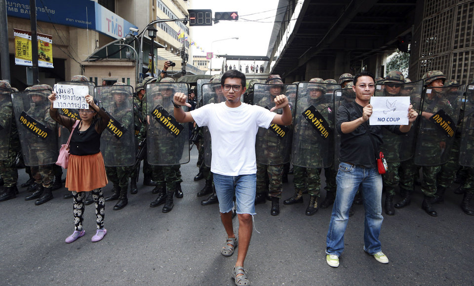 Photo - Protesters walk durng an anti-coup demonstration in front of line of Thai soldiers in Bangkok, Thailand Sunday, May 25, 2014. A spokesman for Thailand's coup leaders said Sunday that democracy had caused