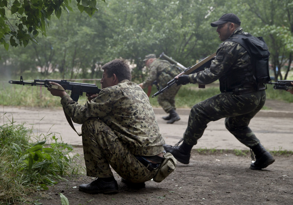Photo - Pro-Russian rebels fire their weapons during clashes during clashes as they attack a border guard base held by Ukrainian troops on the outskirts of Luhansk, eastern Ukraine, Monday, June 2, 2014. Some hundreds of pro-Russia insurgents attacked the base on Monday, with some firing rocket-propelled grenades from the roof of a nearby residential building. At least five rebels were killed when the guards returned fire, a spokesman for the border guard service said. (AP Photo/Vadim Ghirda)