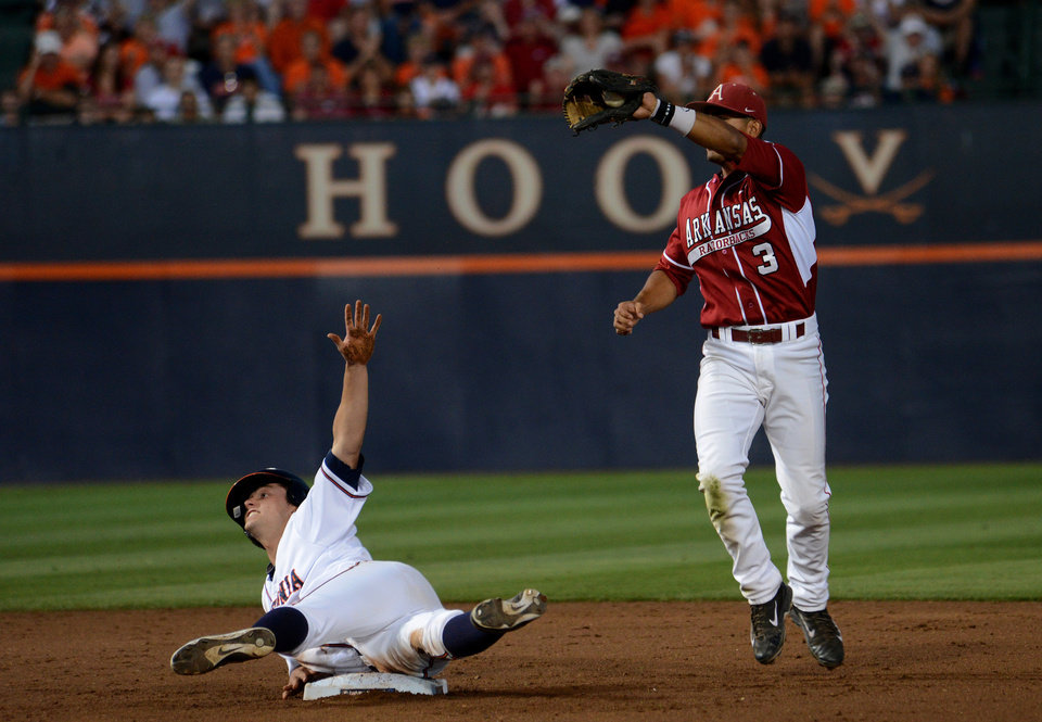 Photo - Virginia's John La Prise, left, motions to the umpire that he is safe as Arkansas' Michael Bernal shows the ball in his glove after he tagged out La Prise at second during the second inning of an NCAA college baseball regional tournament game in Charlottesville, Va., Saturday, May 31, 2014. (AP Photo/Pat Jarrett)