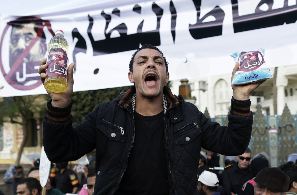 "An Egyptian protester holds up a battle of oil and a bag of sugar as he chants anti-Muslim Brotherhood and Egyptian President Mohammed Morsi slogans outside the presidential palace under a banner with a defaced picture of president Mohammed Morsi and Arabic that reads ""the people want  to bring down the regime,""  in Cairo, Egypt, Saturday, Dec. 8, 2012. Egypt's military has warned of 'disastrous consequences' if the political crisis gripping the country is not resolved through dialogue. Arabic sign on the battle and bag read, ""leave.""(AP Photo/Hassan Ammar)"