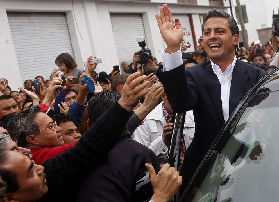 Photo -   Enrique Pena Nieto, top, presidential candidate for the Revolutionary Institutional Party (PRI) waves to supporters after casting his vote during general elections at a polling station in Atlacomulco, Mexico, Sunday, July 1, 2012. Mexico's more than 79 million voters head to the polls Sunday to elect a president, who serves one six-year term, as well as 500 congressional deputies and 128 senators. (AP Photo/Esteban Felix)