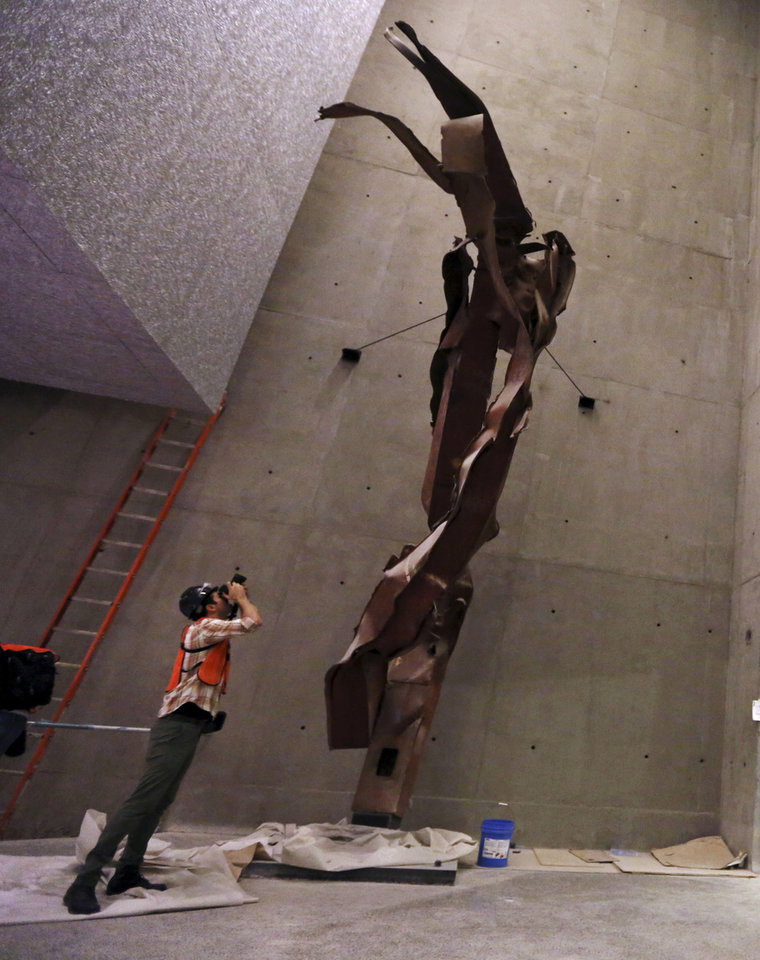 Photo - A photographer take a picture of steel column from the North Tower of the World Trade Center during a media tour of the National September 11 Memorial and Museum, Friday, Sept. 6, 2013 in New York. Construction is racing ahead inside the museum as the 12th anniversary of the Sept. 11, 2001 attacks draws near. Several more large artifacts have been installed in the cavernous space below the World Trade Center memorial plaza. (AP Photo/Mary Altaffer)