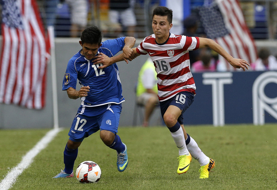 Photo - United States' Jose Torres, right, nudges El Salvador's Andres Flores Mejia out of the way while trying to steal the ball during the second half in the quarterfinals of the CONCACAF Gold Cup soccer tournament on Sunday, July 21, 2013, in Baltimore. The United States won 5-1. (AP Photo/Patrick Semansky)