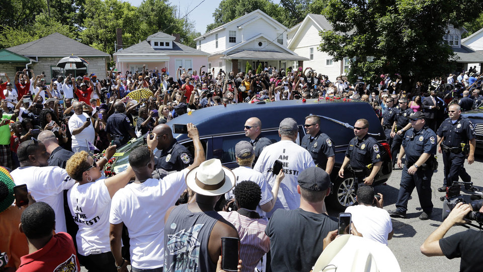 Photo - The hearse carrying the body of Muhammad Ali passes in front of his boyhood home during his funeral procession Friday, June 10, 2016, in Louisville, Ky. (AP Photo/Mark Humphrey)