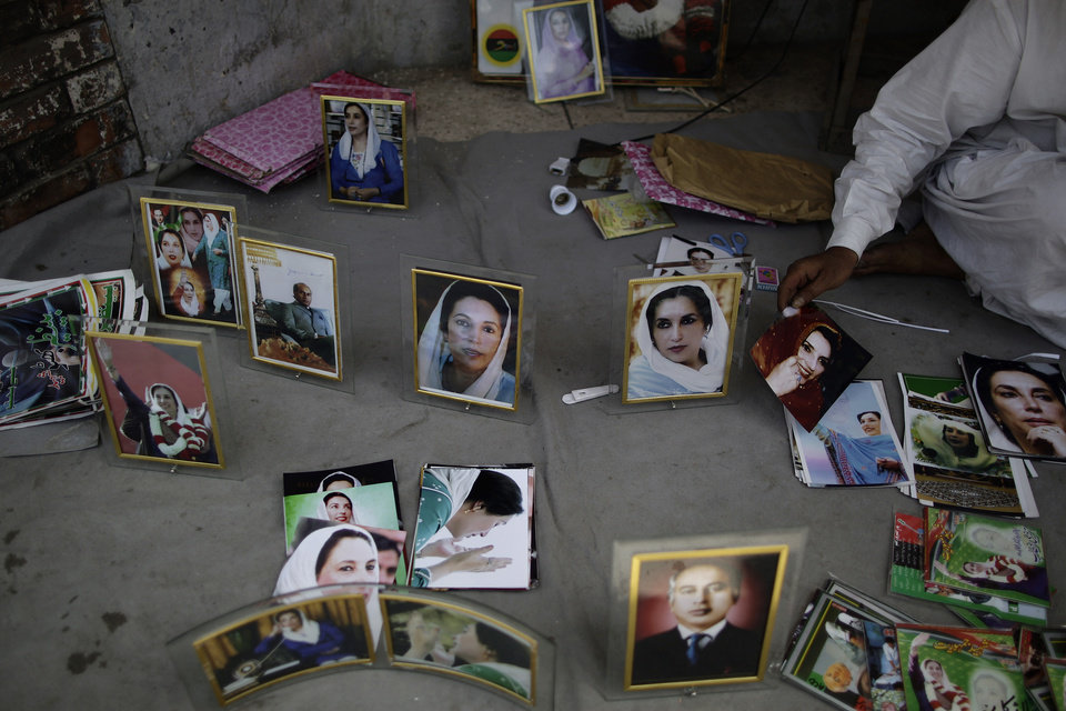 Photo - Pakistani vendor, Mohammed Ashraf, 65, displays photographs of Pakistan's slain leader Benazir Bhutto for sale at the site where she was killed, in Rawalpindi, Pakistan, Monday, April 8, 2013. Pakistan's top court on Monday ordered former military ruler Gen. Pervez Musharraf to respond to allegations that he committed treason while in power and barred him from leaving the country.  The Taliban have threatened to kill him, and he faces a series of legal charges that he has denied, including some related to the 2007 assassination of former Prime Minister Benazir Bhutto. (AP Photo/Muhammed Muheisen)