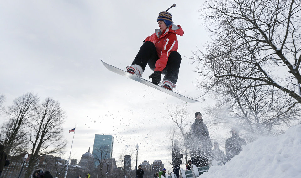 A snowboarder catches some air while taking advantage of a makeshift terrain park on Boston Common in Boston, Saturday, Feb. 9, 2013. The Boston area received about two feet of snow from a winter storm. A howling storm across the Northeast left the New York-to-Boston corridor shrouded in 1 to 3 feet of snow Saturday, stranding motorists on highways overnight and piling up drifts so high that some homeowners couldn\'t get their doors open. More than 650,000 homes and businesses were left without electricity. (AP Photo/Charles Krupa) ORG XMIT: MACK119
