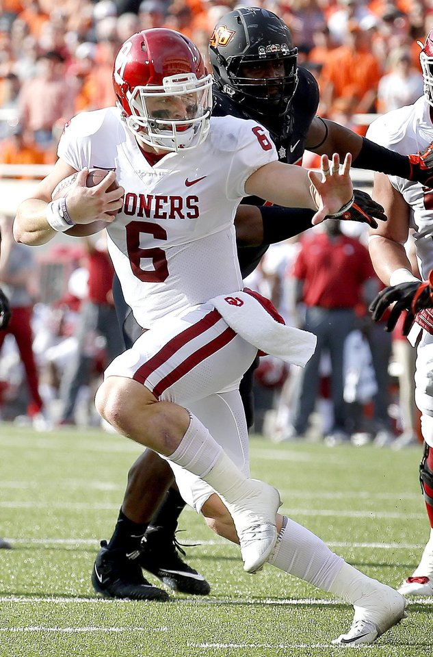 Photo - Oklahoma's Baker Mayfield (6) looks to get by Oklahoma State's Justin Phillips (19) on his way to a touchdown in the second quarter during the Bedlam college football game between the Oklahoma State Cowboys (OSU) and the Oklahoma Sooners (OU) at Boone Pickens Stadium in Stillwater, Okla., Saturday, Nov. 4, 2017. Photo by Sarah Phipps, The Oklahoman