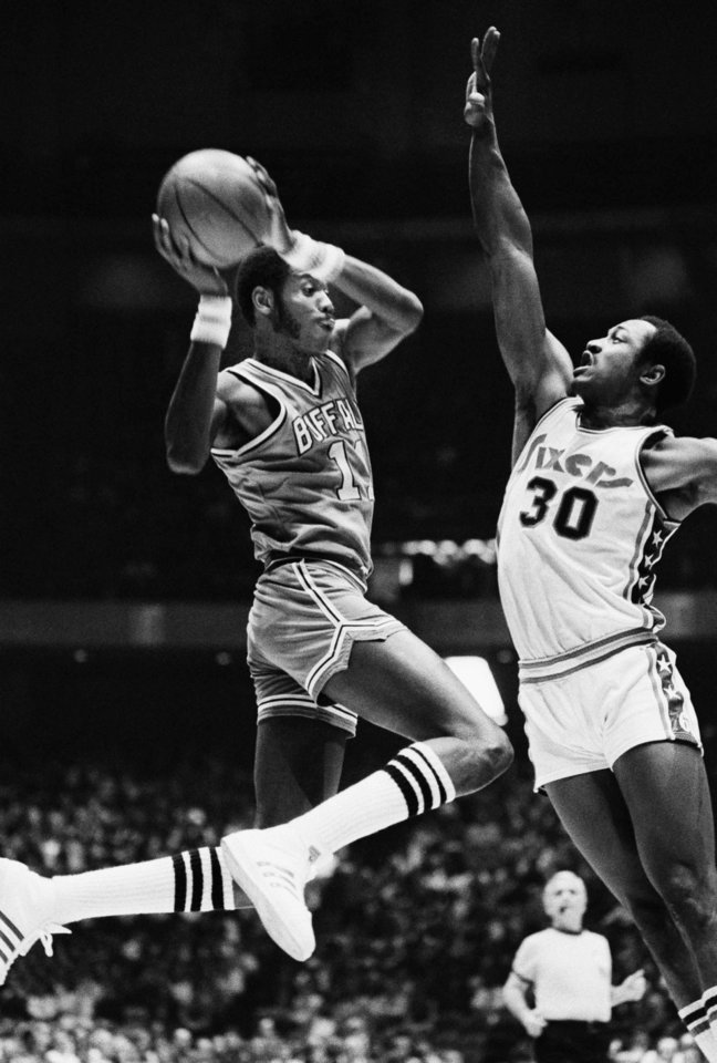 The Buffalo Braves� Bob McAdoo, left, goes to the hoop against Philadelphia�s George McGinnis, right, in 1976. AP photo