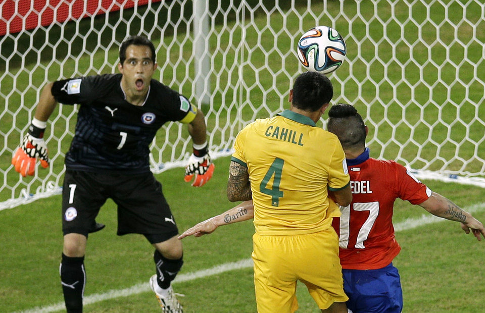 Photo - Australia's Tim Cahill, center, scores a header during the group B World Cup soccer match between Chile and Australia in the Arena Pantanal in Cuiaba, Brazil, Friday, June 13, 2014. (AP Photo/Michael Sohn)