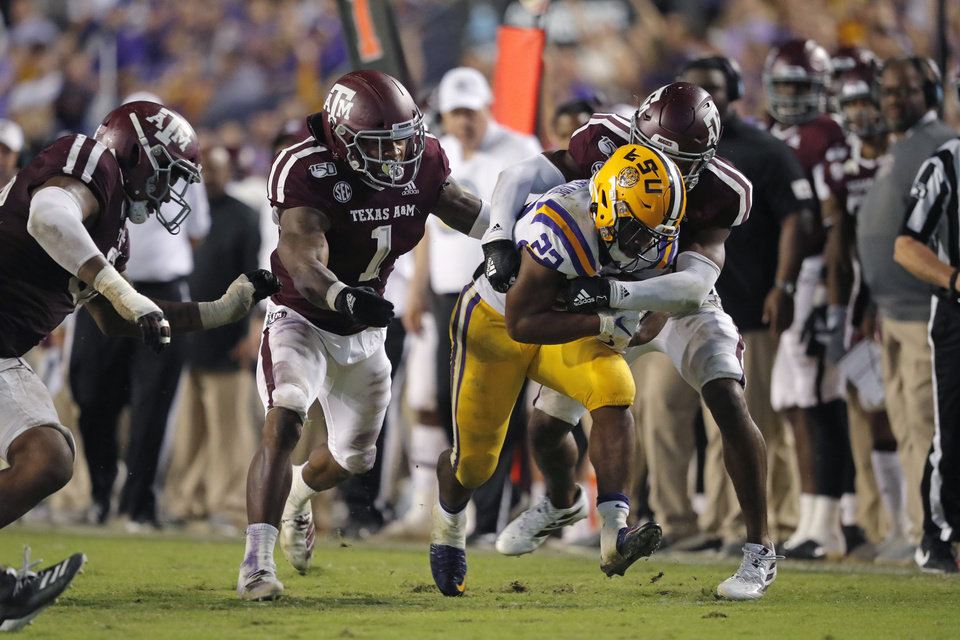 Photo - LSU running back Clyde Edwards-Helaire (22) carries against Texas A&M linebacker Buddy Johnson (1) and defensive back Keldrick Carper during the second half of an NCAA college football game in Baton Rouge, La., Saturday, Nov. 30, 2019. LSU won 50-7. (AP Photo/Gerald Herbert)