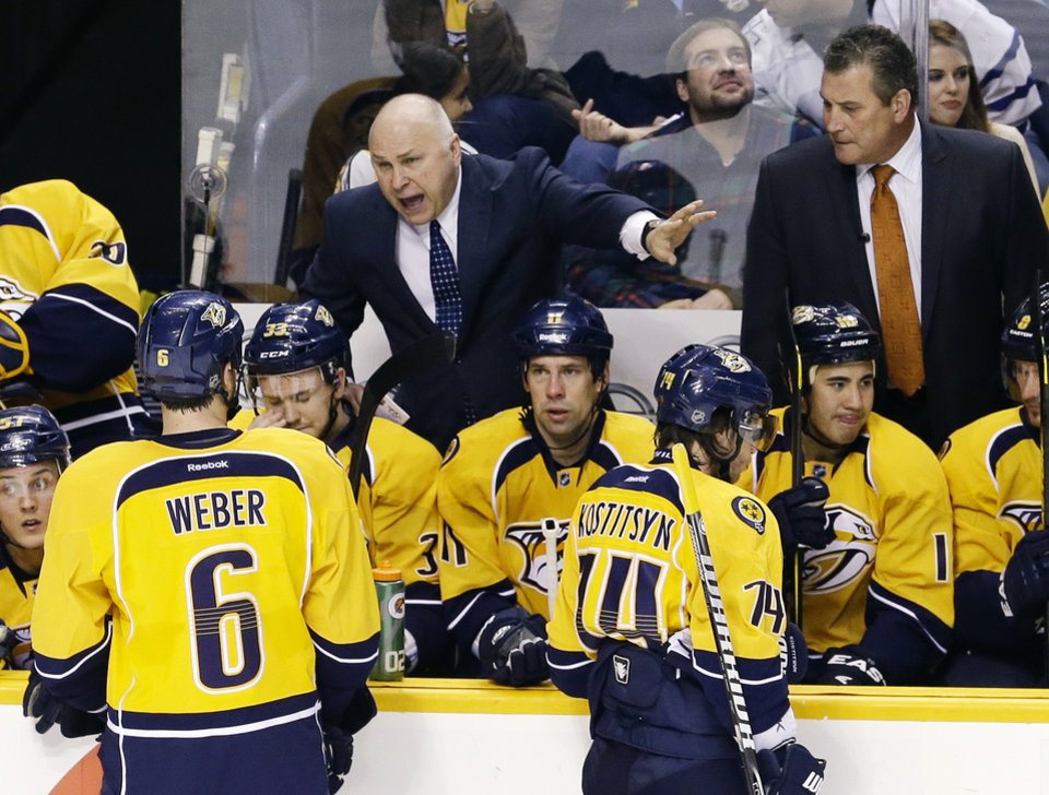 Nashville Predators head coach Barry Trotz, center, talks to his team during a timeout in the second period of an NHL hockey game against the Los Angeles Kings, Thursday, Feb. 7, 2013, in Nashville, Tenn. At right is assistant coach Peter Horachek. (AP Photo/Mark Humphrey)