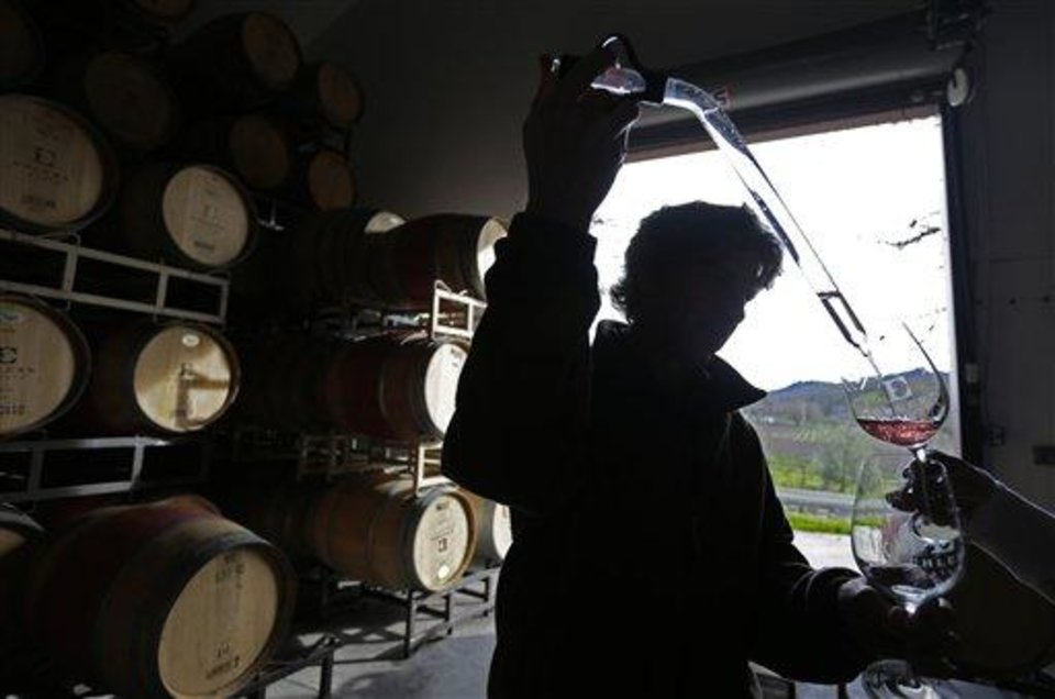 In this photo taken Monday, Jan. 7, 2013, winemaker Kevin Morrisey draws a sample of rose from a barrel at Ehler's Estate in St. Helena, Calif. U.S. wine shipments rose 2 percent last year although foreign wineries captured more of the American wine market, an industry analyst said Wednesday Jan. 30, 2013. (AP Photo/Eric Risberg)