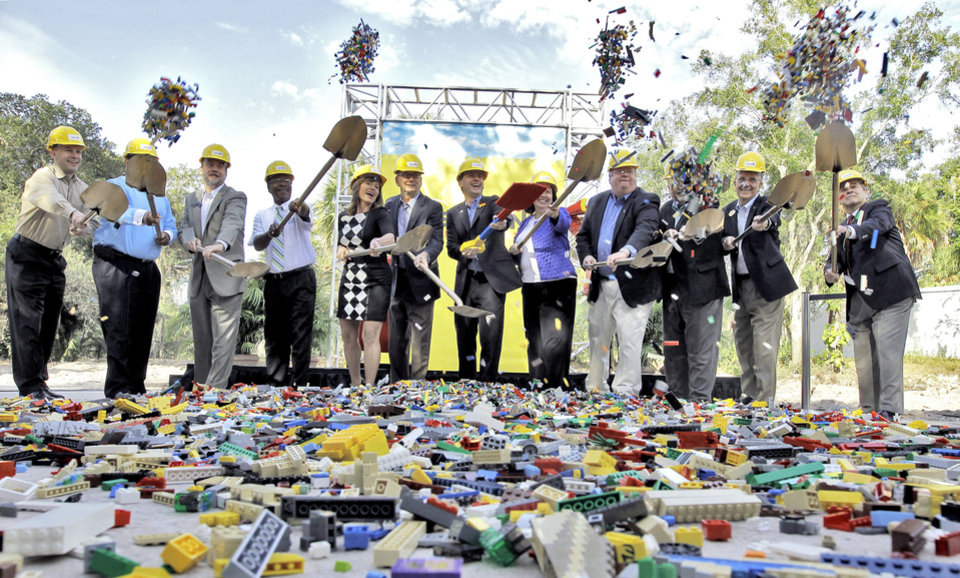 Local dignitaries and officials of Legoland Florida scoop shovels full of Lego blocks as they break ground for a new hotel during a news conference at Legoland Florida Thursday, Nov. 21, 2013, in Winter Haven, Fla. The hotel is scheduled to open in 2015. (AP Photo/Chris O'Meara)