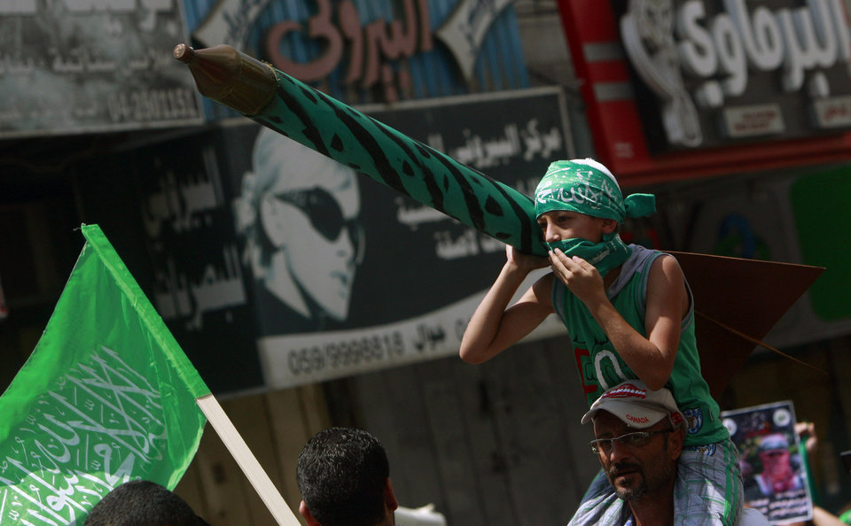 Photo - A Palestinian boy holds a representation of a rocket as supporters of Hamas chant slogans against the Israeli military action in Gaza, during a demonstration in the West Bank city of Jenin on Friday, Aug. 22, 2014. (AP Photo/Mohammed Ballas)