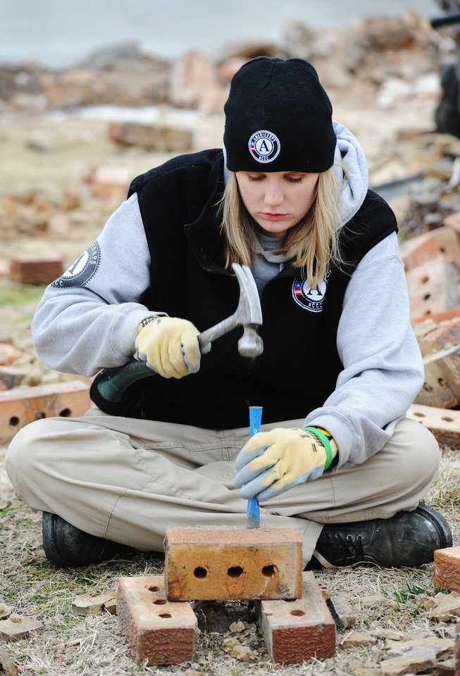 Photo - FILE - In this Jan. 20, 2012 file photo Sarah Riner, from Dalton, Ga., preserves bricks from the Volunteer House in Joplin, Mo. Since the May 22 tornado, thousands of volunteers have come to Joplin to help, including many Joplin natives that have given up careers elsewhere to come home to help with the town's long recovery. (AP Photo/The Joplin Globe, T. Rob Brown, File) ORG XMIT: MOJOP501